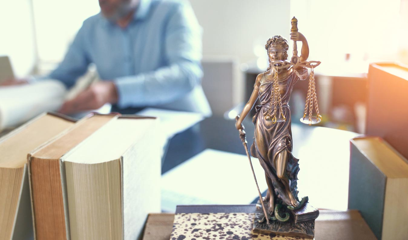 scales of justice with person in background